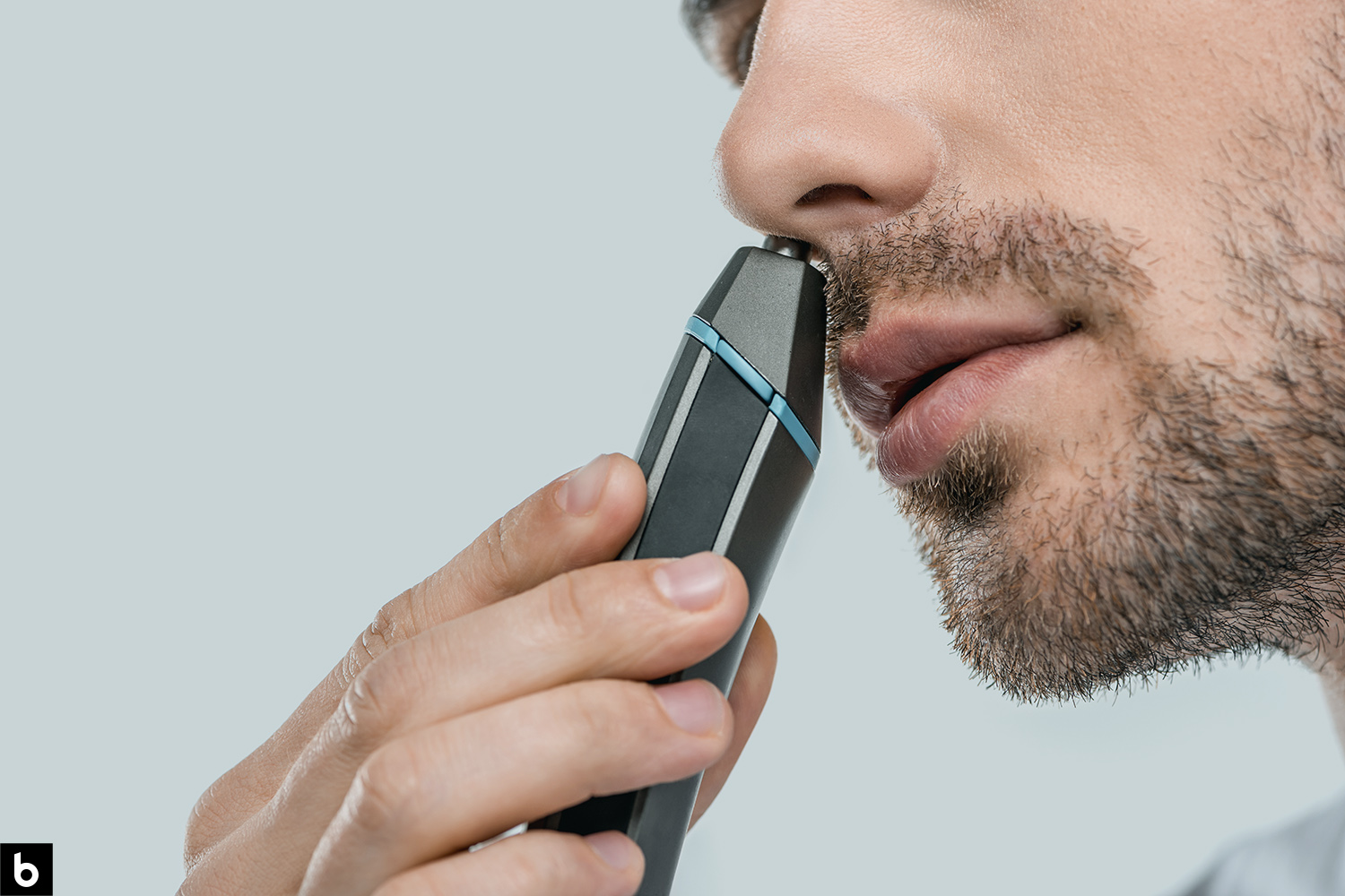 This is the cover photo for our Best Nose Hair Trimmer article. It features a man with facial scruff using a black and blue nose hair trimmer to shave his nose.