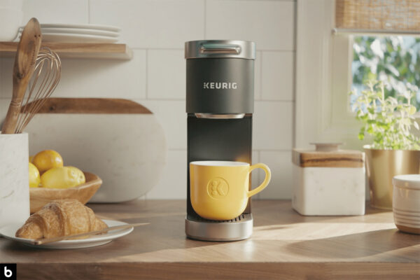 This is the cover photo for our Best Single Serve Coffee Maker article. It features a Keurig coffee maker with a light yellow cup. There a various other items on the kitchen counter, including a jar of utensils, a plate of pastries, and several plants.