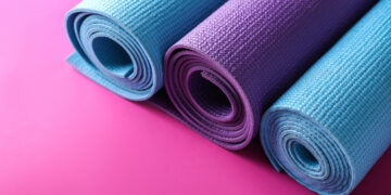 This is the cover photo for our Best Yoga Mats article. It features 3 rolled up yoga mats on top of a pink background.