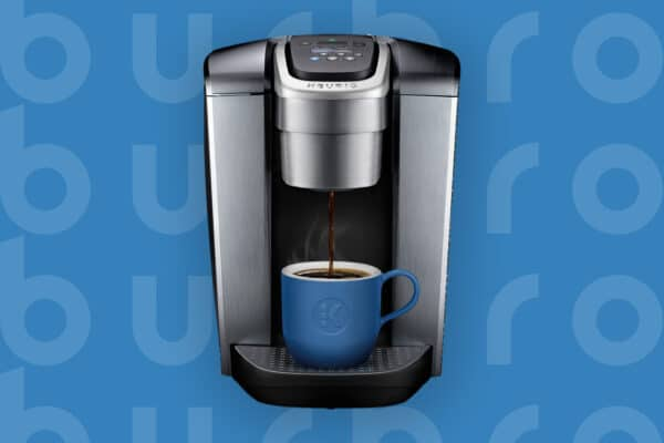 This is the cover photo for our Best Coffee Maker article. It features a metallic silver Keurig coffee maker overlaying a blue poster background with an embossed Burbro logo.