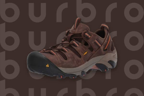This is the cover photo for our Best Shoes for Standing/Working on Concrete article. It features a rugged, brown and black hiking boot overlaying a brown background with an embossed Burbro logo.