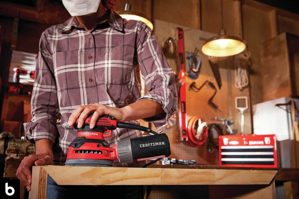 This is a photo for the Best Palm Sander 2021 buying guide. Man sanding a board with a palm sander in his garage. There are several power tool in the background.