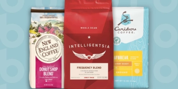 This is the cover photo for our Best Coffee Brands article. It features a bag of New England Coffee, a bag of Intelligentsia Coffee, and a bag of Caribou Coffee, all overlaid on a blue background with an embossed Burbro logo.