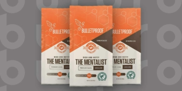 This is the cover photo for our Best Coffee for French Press article. It features three bags of The Mentalist Whole Bean coffee, overlaying a grey background with an embossed Burbro logo.