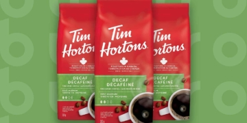 This is the cover photo for our Best Decaf Coffee article. It features 3 red bags of Tim Hortons coffee overlaid on a fresh green background with an embossed Burbro logo.