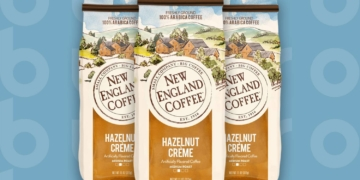 This is the cover photo for our Best Flavored Coffee article. It features three bags of New England Coffee Hazelnut Crème flavored coffee, overlaid on a blue background with embossed Burbro logo.