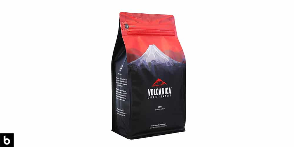 This is a product image for our Best Flavored Coffee 2021 article. It features a red and navy bag of Volcanica Hazelnut roast coffee beans.