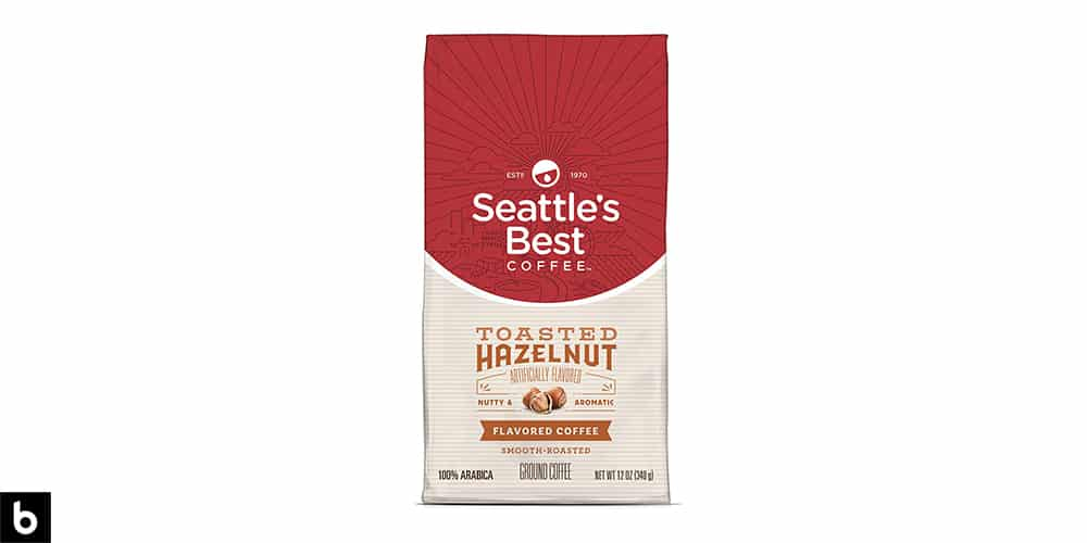 This is a product image, featuring a red and cream colored bag of Seattle's Best Toasted Hazelnut flavored coffee.
