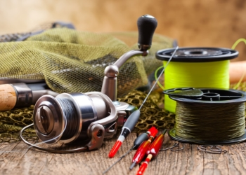 This is the cover photo for our Best Braided Fishing Line article. It features a couple spools of braided fishing line on a table, with a fishing rod, and assorted fishing tackle.