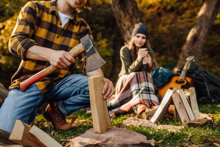This is the cover photo for our Best Camping Axes / Hatchets article. It features a photo of a guy splitting wood by a campfire with a girl in the background sitting next to a bonfire.