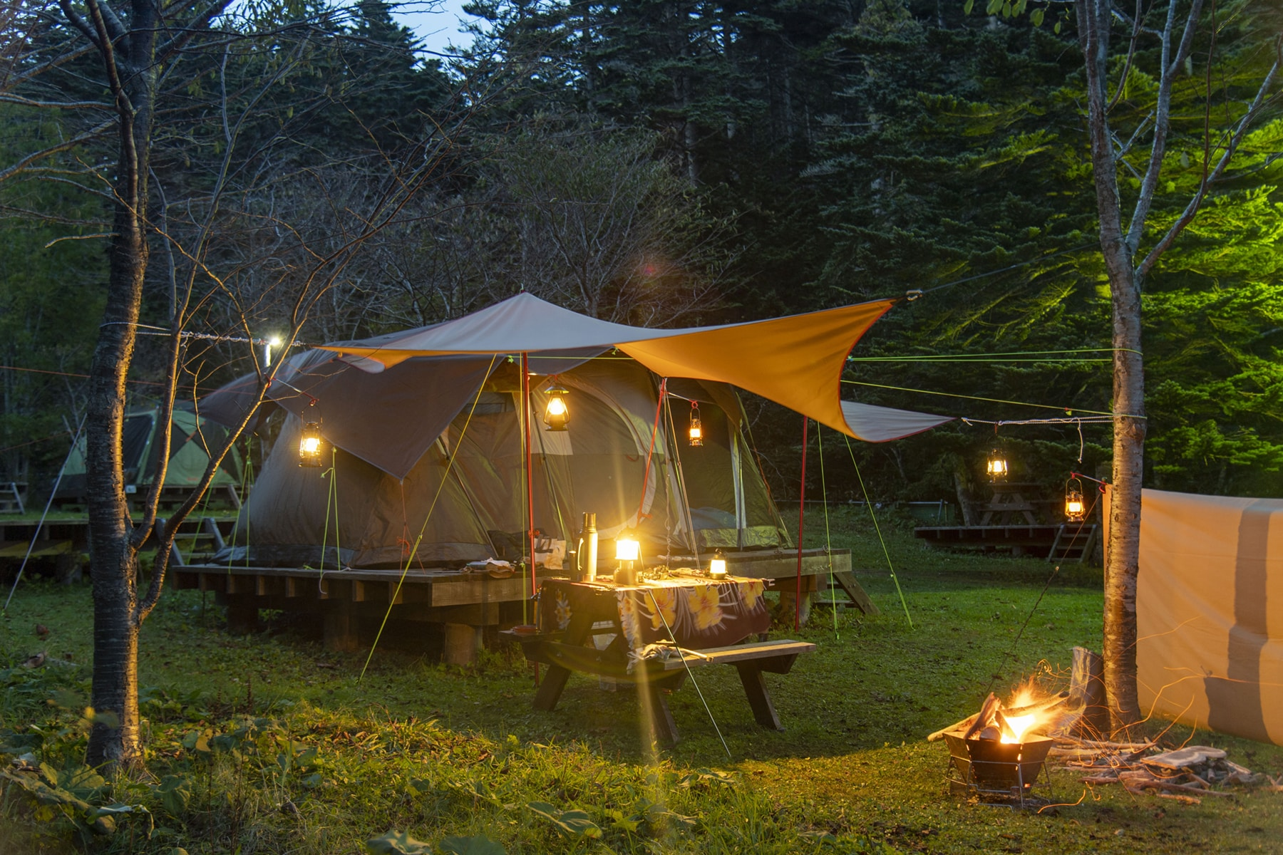 This is the cover photo for our Best Camping Tart article. It features a tent, camping tarp, and campfire in the woods.