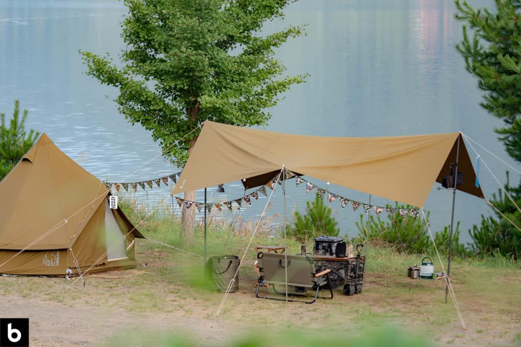 This is the buying guide for our Best Camping Tarp 2021 article. It features a green tent and canopy at a camping site beside a lake.