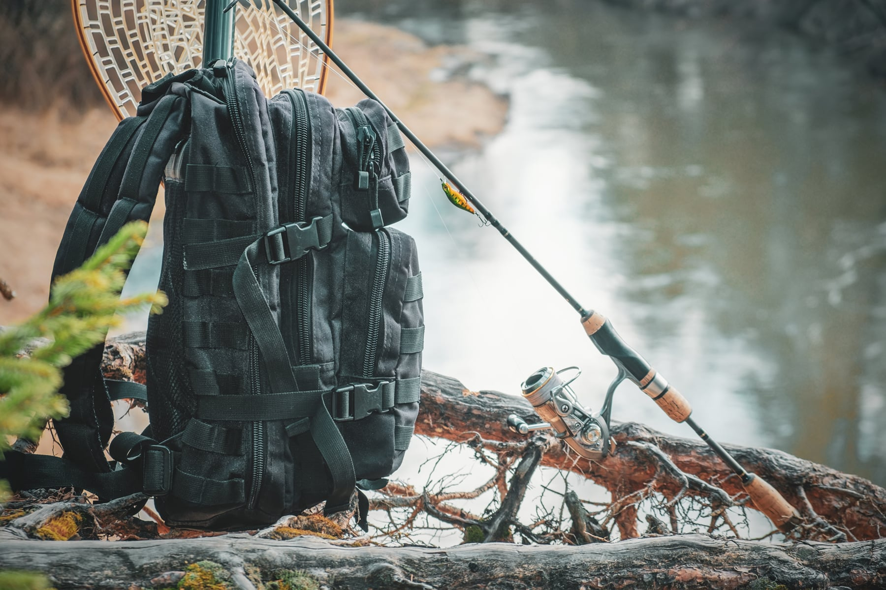 This is the cover photo for our Best Fishing Tackle Backpacks article. It features a tackle backpack and fishing rod on a river bank with a river and trees in the background.