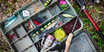 This is the cover photo for our Best Tackle Box article. It features a tackle box on the ground with fishing lures and assorted accessories inside.