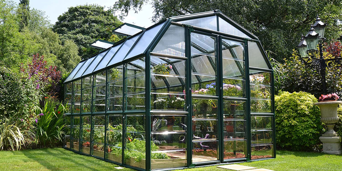 This is the cover photo for our Best Greenhouse Kits article. It features a greenhouse with plants inside, situated in a garden with green grass, trees, bushes, and flowers.