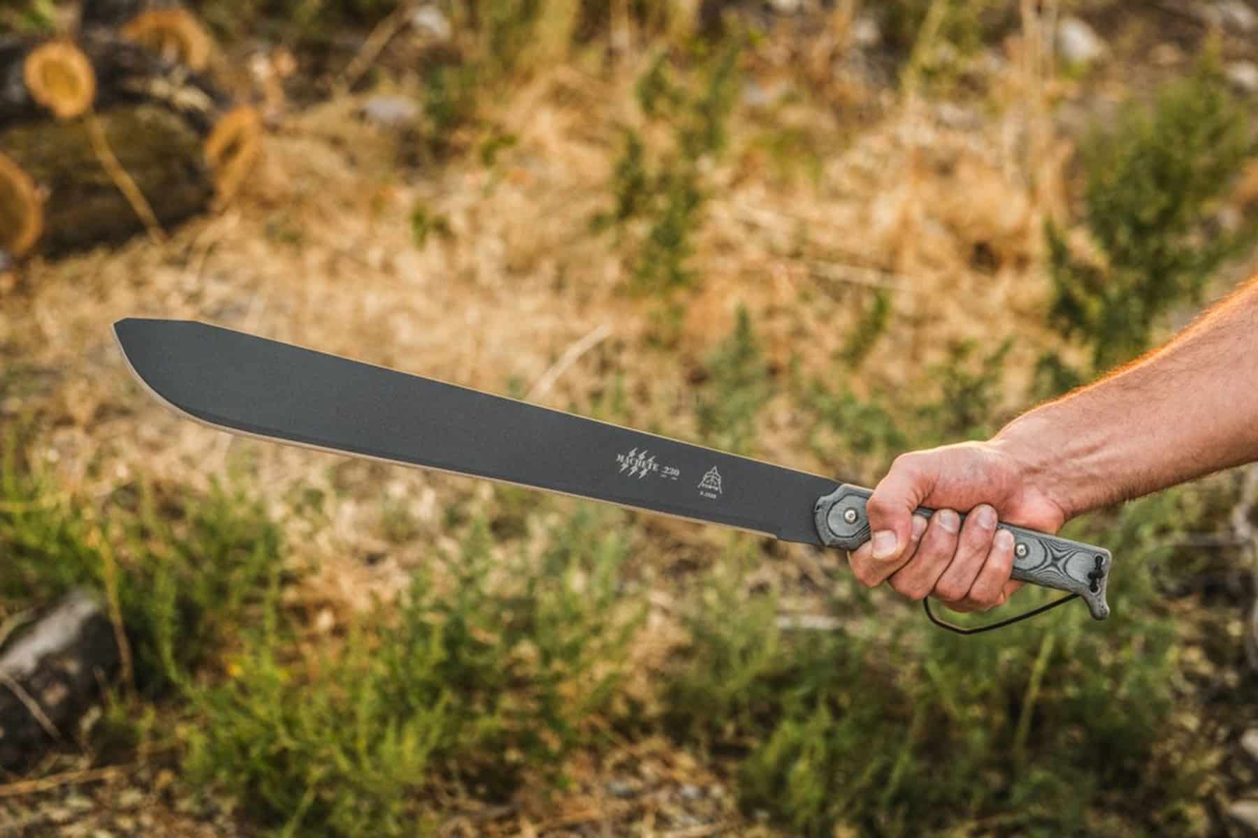 This is the cover photo for our Best Machetes article. It features a man's arm holding a metal machete with grass and trees in the background.