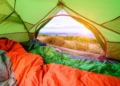 This is the cover photo for our Best Sleeping Bags articles. It features orange and green sleeping bags inside a green tent, with the front flap open to a scenic view outside.