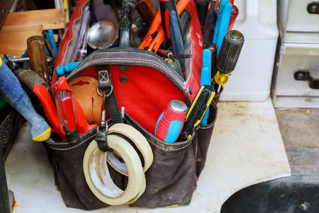 This is the featured image for our Best Tool Bag 2021 Buying Guide. It features a red and black tool bag full of tools placed on the ground.
