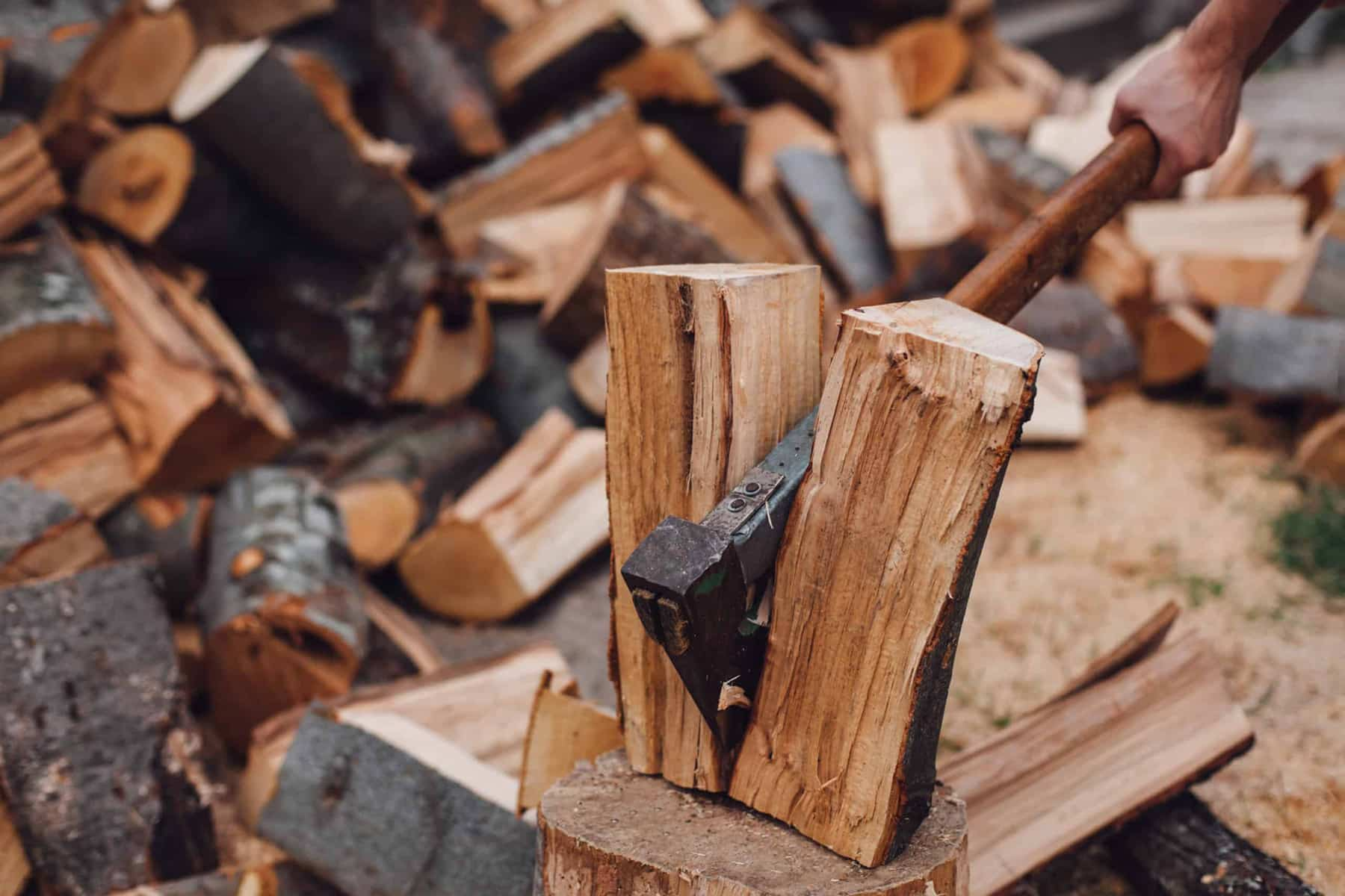 This is the cover photo for our Best Wood Splitting Axe article. It features an axe splitting a log with a pile of split wood in the background.