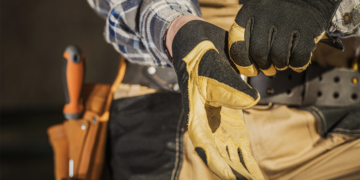 This is the cover photo for our Best Work Gloves article. It features a person putting on a pair of black and tan leather work gloves.
