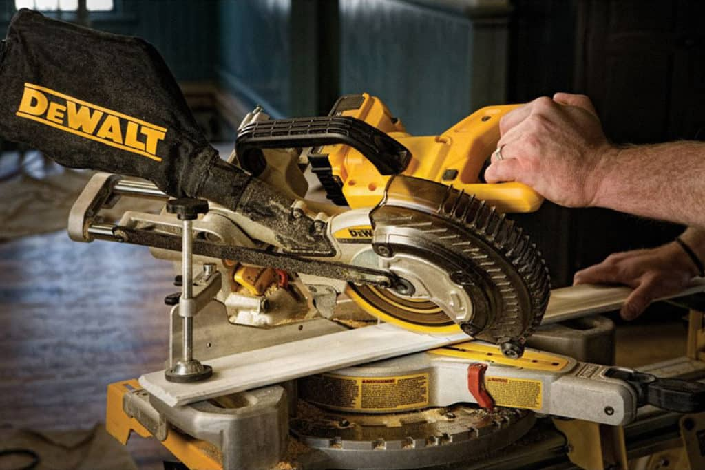 This is a photo for our Best Dewalt Miter Saw 2021 article. It features a photo of a person cutting trim on a table-mounted yellow miter saw.